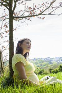 אישה בהריון יושבת ליד עץ