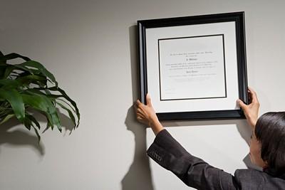 אשת עסקים תולה תמונה על הקיר